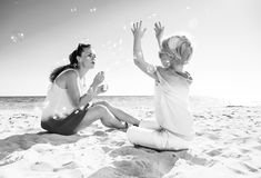 Smiling trendy mother and daughter on seacoast blowing bubbles. Colorful and wonderfully cheerful mood. smiling trendy mother and daughter in colorful clothes on stock photography