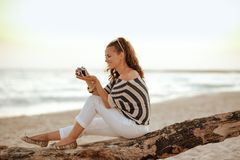 Solo traveller woman viewing photos on camera. Smiling trendy solo traveller woman in white pants and striped blouse on the beach at sunset viewing photos on royalty free stock photo
