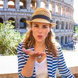 Smiling trendy traveller woman in Rome, Italy blowing air kiss Stock Images