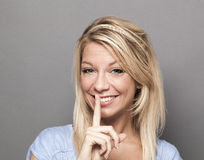Smiling trendy woman asking to keep quiet for discretion Stock Photography