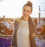 Smiling trendy woman in coat at Guell Park in Barcelona, Spain Stock Photo