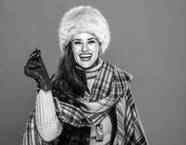 Smiling trendy woman  on cold blue snapping fingers. Winter things. Portrait of smiling trendy woman in fur hat  on cold blue snapping fingers Stock Photo