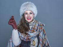 Smiling trendy woman isolated on cold blue snapping fingers. Winter things. Portrait of smiling trendy woman in fur hat isolated on cold blue snapping fingers Stock Photos