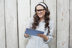 Smiling trendy woman with stylish glasses using her tablet Stock Photos