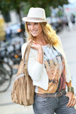 Smiling trendy woman wearing leather bag and white hat Royalty Free Stock Image