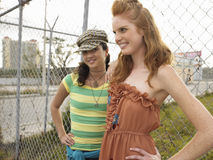 Smiling Trendy Women Standing By Fence Stock Photography