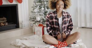 Smiling trendy young woman enjoying Christmas. Smiling trendy young African woman enjoying Christmas sitting on the floor in front of the decorated tree in the stock video footage