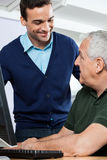 Smiling Tutor Looking At Senior Student In Computer Class. Smiling young tutor looking at senior male student at desk in computer class Royalty Free Stock Photo