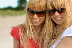 Smiling twins. Portrait of smiling blond twins on the beach Royalty Free Stock Photos