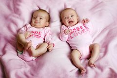 Smiling twins on a blanket. Some cute fraternal twins on a pink blanket stock image