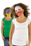 Smiling twins fans. With painted Polish and  Slovakian flags on faces. They're looking at camera. Focus on first person. They're on white background. Front view Stock Image