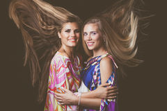 Smiling two blonde young women beauty  portrait with hair in mot Stock Photo