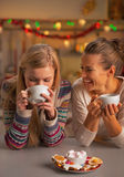 Smiling two girlfriends having christmas snacks in kitchen Stock Images