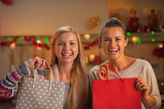 Smiling two girlfriends with shopping bag in kitchen Stock Image