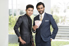 Smiling two Indian businessman with rupees Royalty Free Stock Photos
