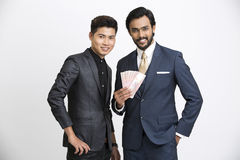 Smiling two Indian businessman with rupees. On white background Royalty Free Stock Photography