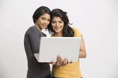Smiling two Indian young women working posing with laptop Stock Photography