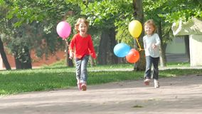 A smiling two little sisters with balloons running. In the park. Surrounded by greenery, Happy Family on a Walk in Summer. Slow motion stock footage