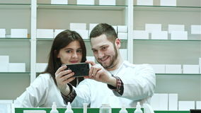 Smiling two pharmacist taking selfie in pharmacy stock footage