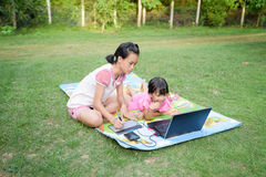 Smiling two sister using laptop outdoor. Smiling family using laptop and tablet with stylus together outdoor Royalty Free Stock Images