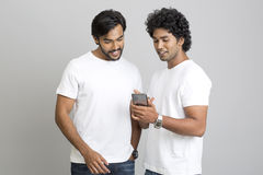 Smiling two young men standing and using smartphone Stock Photos