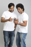 Smiling two young men standing and using smartphone Stock Photo