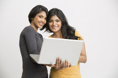 Smiling two young women working posing with laptop Stock Photos