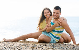 Smiling twosome having romantic date on beach Stock Image