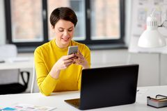 Smiling ui designer using smartphone at office royalty free stock photo