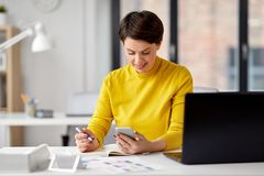 Smiling ui designer using smartphone at office royalty free stock photography