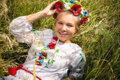 Smiling ukrainian girl in national clothes lying on field Stock Image