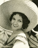 Smiling under her straw hat Stock Images