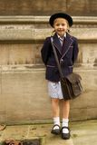 Smiling uniformed schoolgirl leaning against stone wall Royalty Free Stock Images