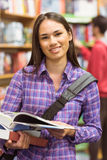 Smiling university student holding textbook Royalty Free Stock Image