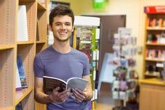 Smiling university student holding textbook Royalty Free Stock Photos