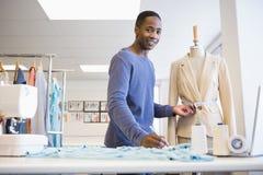 Smiling university student measuring waist of model Royalty Free Stock Image