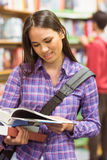 Smiling university student reading textbook Royalty Free Stock Photos