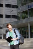 Smiling university student standing outside with notepad Royalty Free Stock Photos