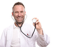 Smiling unshaven male doctor holding a stethoscope. Smiling unshaven male doctor holding up the disc of a stethoscope in his hand ready to do an examination as stock image