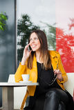 Smiling urban girl sit in cafe talking on smartphone Royalty Free Stock Image