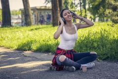 Smiling urban girl sitting on skateboard and listening music. Outdoors, urban lifestyle. Smiling urban girl sitting on skateboard on street and listening music stock image