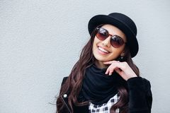 Smiling urban girl with smile on her face. Portrait of fashionable gir wearing a rock black style having fun outdoors Stock Photography