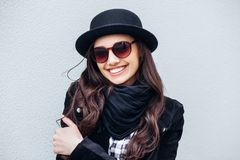 Smiling urban girl with smile on her face. Portrait of fashionable gir wearing a rock black style having fun outdoors Royalty Free Stock Photography