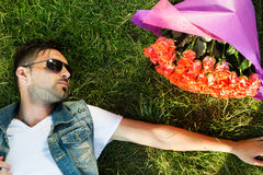 Smiling valentine male with bunch of roses lying on grass Royalty Free Stock Photography