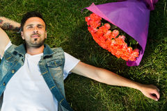 Smiling valentine male with bunch of roses lying on grass. Romantic young boy lying on grass with roses Stock Images