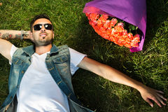 Smiling valentine male with bunch of roses lying on grass. Young guy lying on gras with bouquet of roses Stock Photography