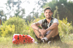 Smiling valentine male with bunch of roses sitting on grass. Happy romantic guy sitting on grass with roses Royalty Free Stock Photos