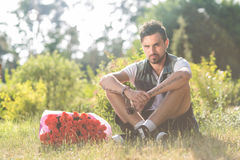 Smiling valentine male with bunch of roses sitting on grass. Young romantic guy with bouquet of roses Stock Photos
