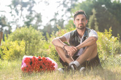 Smiling valentine male with bunch of roses sitting on grass Royalty Free Stock Images