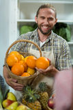 Smiling vendor offering oranges at the counter. In grocery store Royalty Free Stock Photos